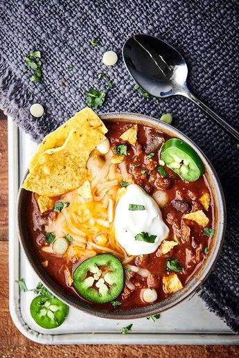 This Instant Pot Chili Recipe is SO quick, easy, and loaded with bacon, beef, beer (optional), broth, tomato sauce, veggies, beans, and spices! Serve with optional, but highly recommended cornbread, shredded cheese, and sour cream! SO hearty and cozy. showmetheyummy.com #instantpot #beef #chili