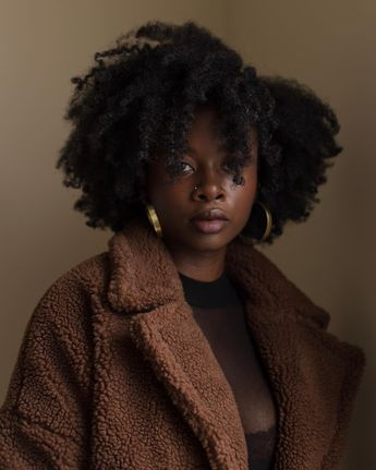Black woman with natural hair in a brown teddy coat with gold hoop earrings