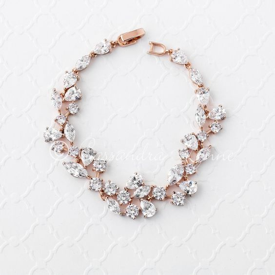 This CZ bridal bracelet is designed with round, teardrop and marquise jewels. Classic wedding day style or for any special occasion. Locking clasp, 7 inches long and .75 inches wide. Available in rhodium, gold or rose gold plate, AAA grade CZ, lead free.