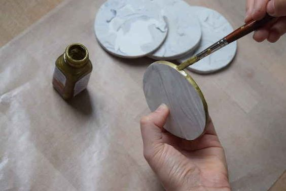 Apply two coats of gold paint around the coaster edges and let dry for at least 20 minutes.