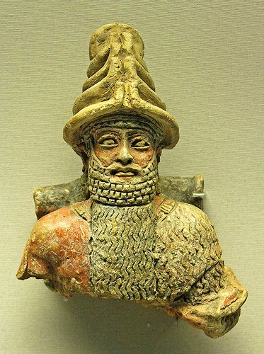 Statue of a god. Fragment of a painted clay statue of a seated unidentified god,wearing homed headdress characteristic of Mesopotamian deity.Found in Ur,Iraq.about 2000-1750 BC
