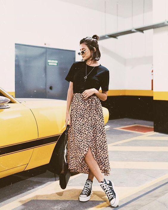 Chica con falda de estampado animal y camiseta negra.
