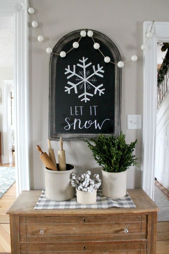 Farmhouse winter touches - Let it Snow hand lettered chalkboard with vintage crocks, rolling pins, cotton stems and greenery
